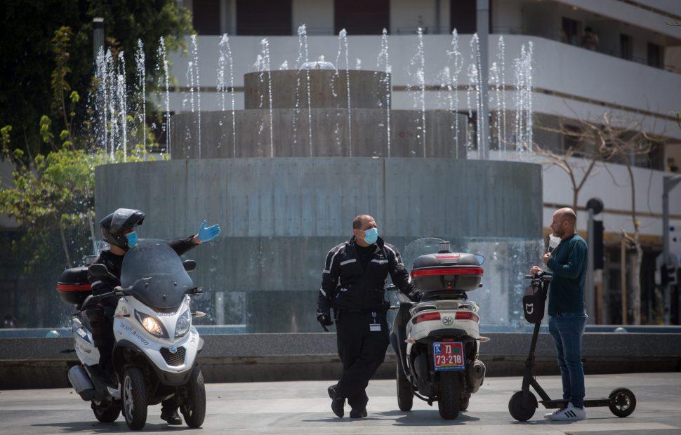 שוטר נותן דו״ח על אי חבישת מסיכה // צילום: מרים אלסטר - Flash 90