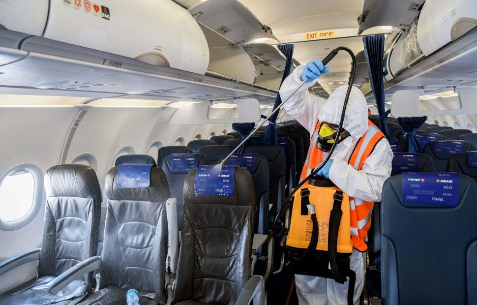 עובד נמל התעופה מחטא מטוס נוסעים לקראת טיסה בשגרת הקורונה - צילום יוסי זליגר / Flash90